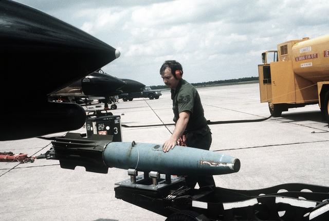 AN airman walks beside a 500-lb. Mark 82 hi-drag bomb, being carried to an F-4 Phantom II aircraft by a bomb loader driver. The airman is assigned to the 128th Tactical Fighter Squadron, 116th Tactical Fighter Wing, Texas Air National Guard, involved in exercise Gangbuster XI