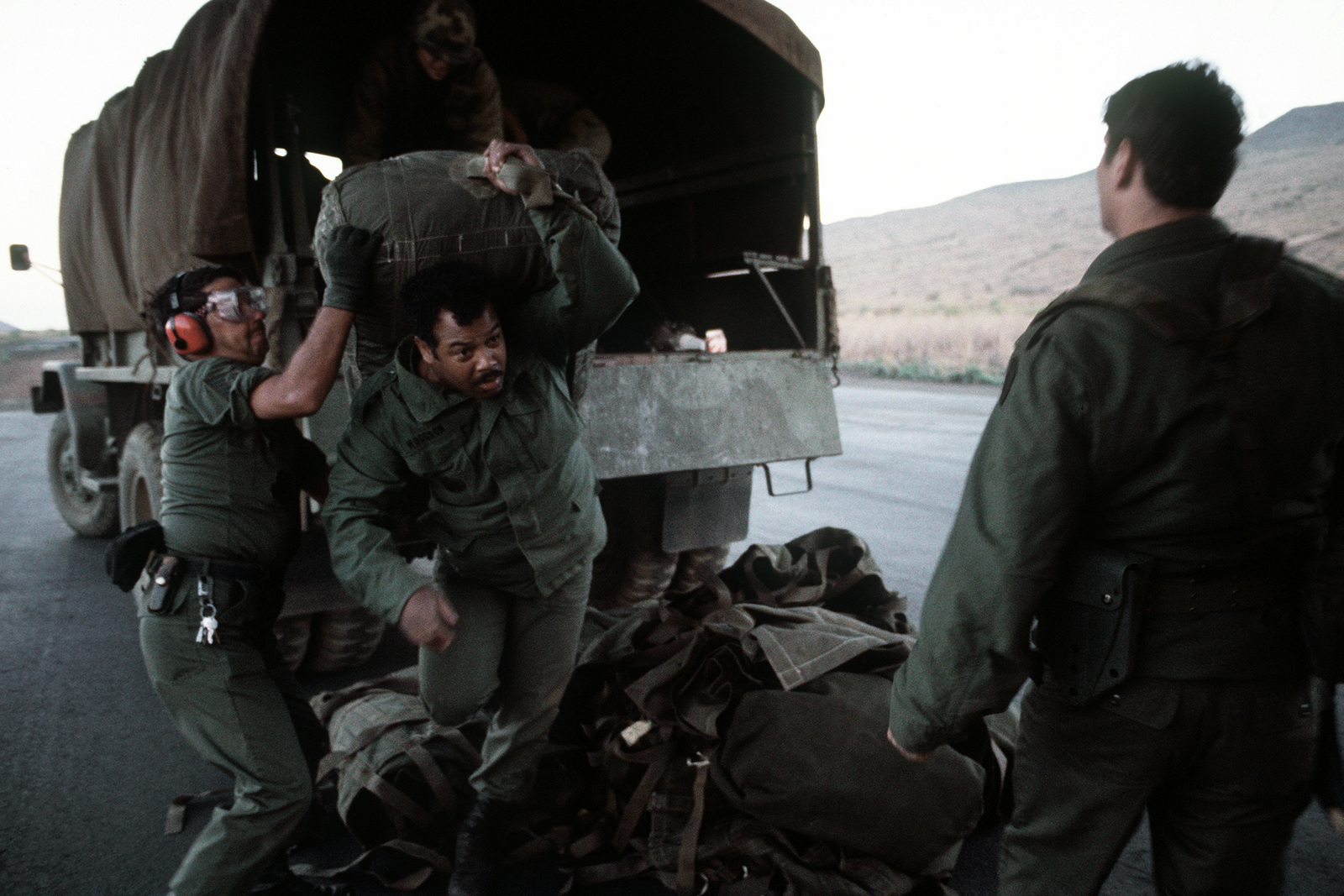 25th Infantry Battalion members load cargo aboard a C-130 Hercules aircraft from an Army truck during Joint Airborne Airportability Tactical Training