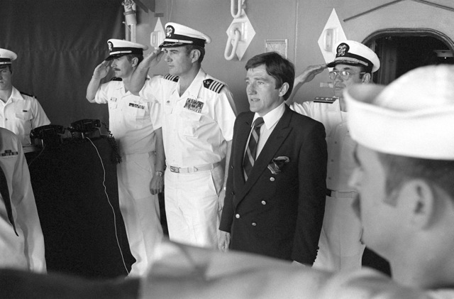 Secretary of the Navy John F. Lehman Jr., center, stands as officers and crewmen salute the colors during his visit aboard the aircraft carrier USS KITTY HAWK (CV-63)