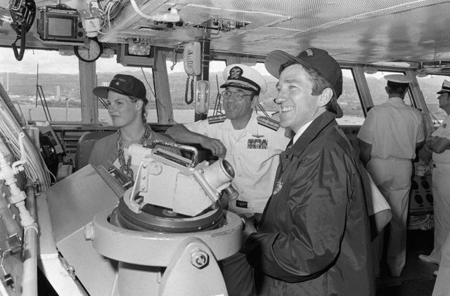 Secretary of the Navy John F. Lehman Jr., right, Mrs. Lehman, and RDML Lawrence C. Chambers visit the bridge of the aircraft carrier USS KITTY HAWK (CV-63)