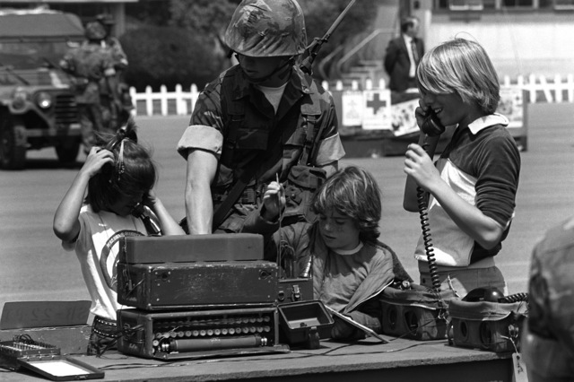 Lance CPL. Holmes of the 1ST Battalion, 1ST Marines, demonstrates the use of a field switchboard (SB-22) and a field telephone (TA-312/PT) to three children during Family Day