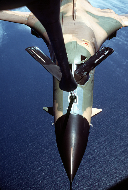 Front view of a B-1 bomber aircraft being refueled by a KC-135 Stratotanker aircraft over the water off the California coast, as seen from the boom operator's section, during testing and evaluation. The Stratotanker is assigned to the 22nd Bomb Wing