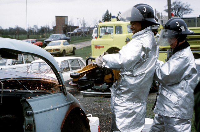 Firemen use a K-12 circular saw to cut off the top of a car during crash victim extrication training