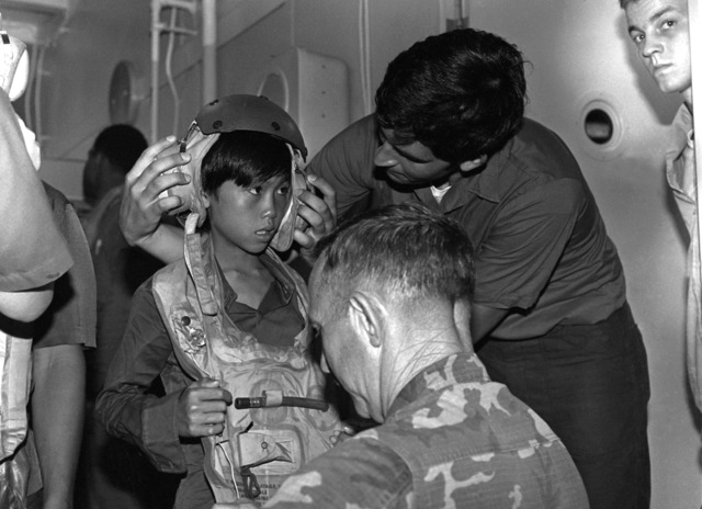 Prior to the arrival of the amphibious assault ship USS BELLEAU WOOD (LHA-3) in Singapore, the Vietnamese people are being given life preservers and flight deck crewmen helmets for the transfer to the dock landing ship USS THOMASTON (LSD-28)