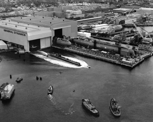 An aerial port quarter view of the nuclear-powered attack submarine CITY OF CORPUS CHRISTI (SSN-705) sliding into the water at the conclusion of the launching ceremony. In the background is the nuclear-powered strategic missile submarine FLORIDA (SSBN-728) under construction