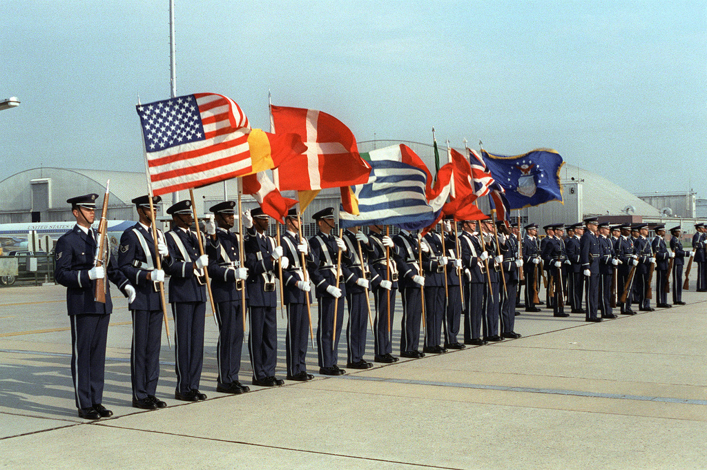 An honor guard, holding flags of NATO countries, perform at