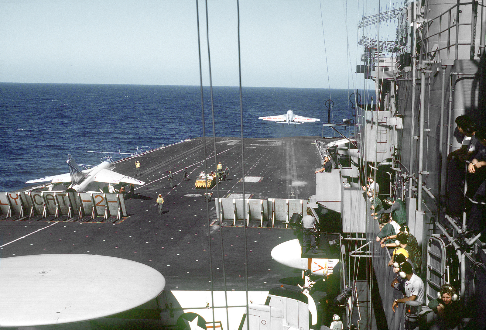 A rear view of an F-4 Phantom II aircraft being launched and an A-7 Corsair II aircraft awaiting launch from the flight deck of the aircraft carrier USS CORAL SEA (CV-43)