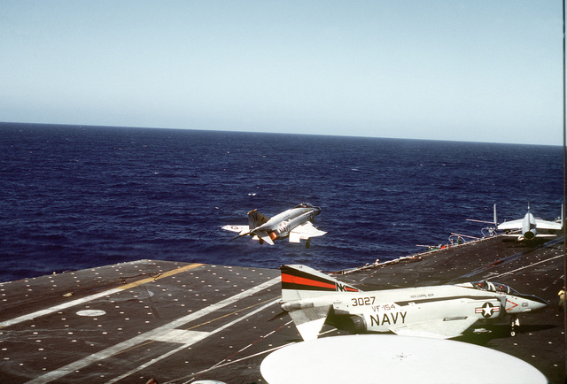 A right rear view of an F-4 Phantom II aircraft from Fighter Squadron 21 (VF-21) being launched from the flight deck of the aircraft carrier USS CORAL SEA (CV-43)