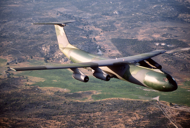 """AN air-to-air left front view of a C-141B Starlifter aircraft with the new European paint scheme. The aircraft is nicknamed """"Green Lizard"""""""