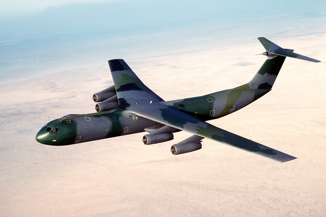"""AN air-to-air left side view of a C-141B Starlifter aircraft with the new European paint scheme. The aircraft is nicknamed """"Green Lizard"""""""