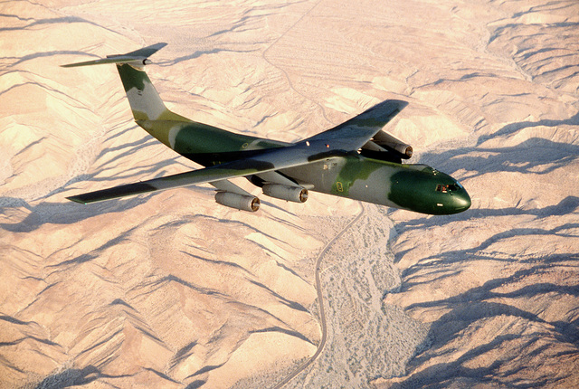 """AN air-to-air right front view of a C-141B Starlifter aircraft with the new European paint scheme. The aircraft is nicknamed """"Green Lizard"""""""