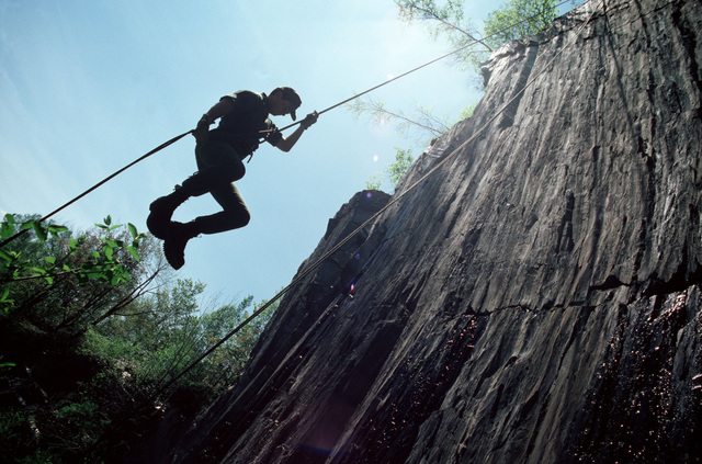 An infantryman rappels down a cliff during a field training exercise