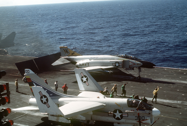 An overhead right side view of an F-4 Phantom II aircraft from Fighter Squadron 21 (VF-21) and an A-7 Corsair II aircraft from Attack Squadron 97 (VA-97) during preflight preparations on the flight deck of the aircraft carrier USS CORAL SEA (CV-43)