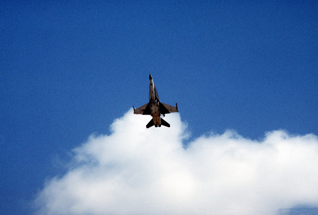 An underside view of an F-18 Hornet aircraft during flight demonstrations at the air show