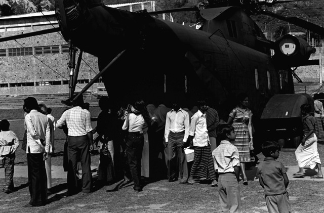 Early arrivals leave the CH-53 Sea Stallion helicopter that was put on display after the airlift of television parts for the Sri Lankan television station. Many other people stand to the rear of the aircraft. The Marines and the helicopters are from Marine Medium Helicopter Squadron 165 (HMM-165)