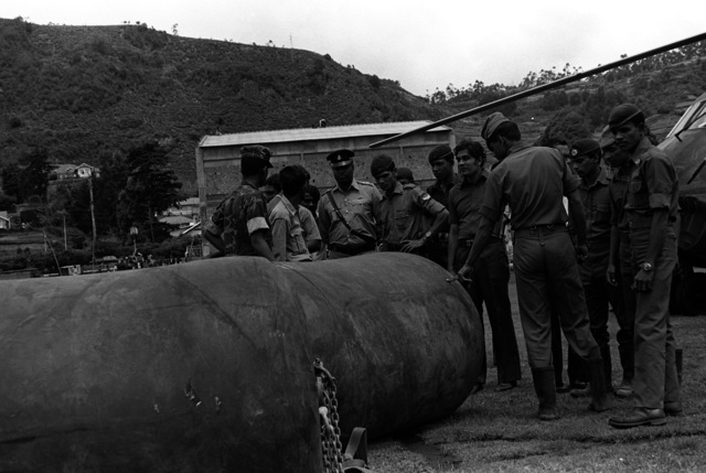 U.S. Marines and members of the military of Sri Lanka talk together as they look over the heavy rubber fuel bags that are used to refuel the helicopters. The Marines and the helicopters are from Marine Medium Helicopter Squadron 165 (HMM-165)