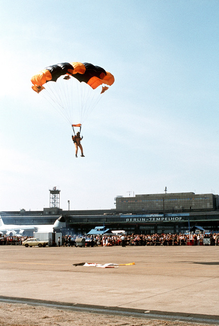 A member of the Yellow Knight parachute team descends to a marked point before a crowd during the open house