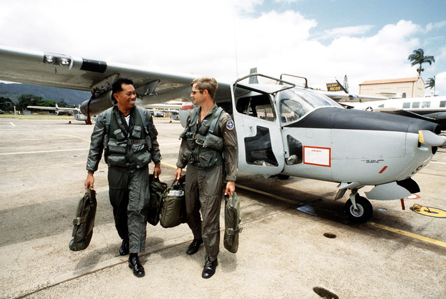 Group CPT Prakob Sudprapai, deputy of technical service security forces, Royal Thai Air Force, left, and CPT Joe Sovich of the 22nd Tactical Air Support Squadron, walk away from an O-2 Skymaster aircraft after a flight. The two men are participants in a joint exercise