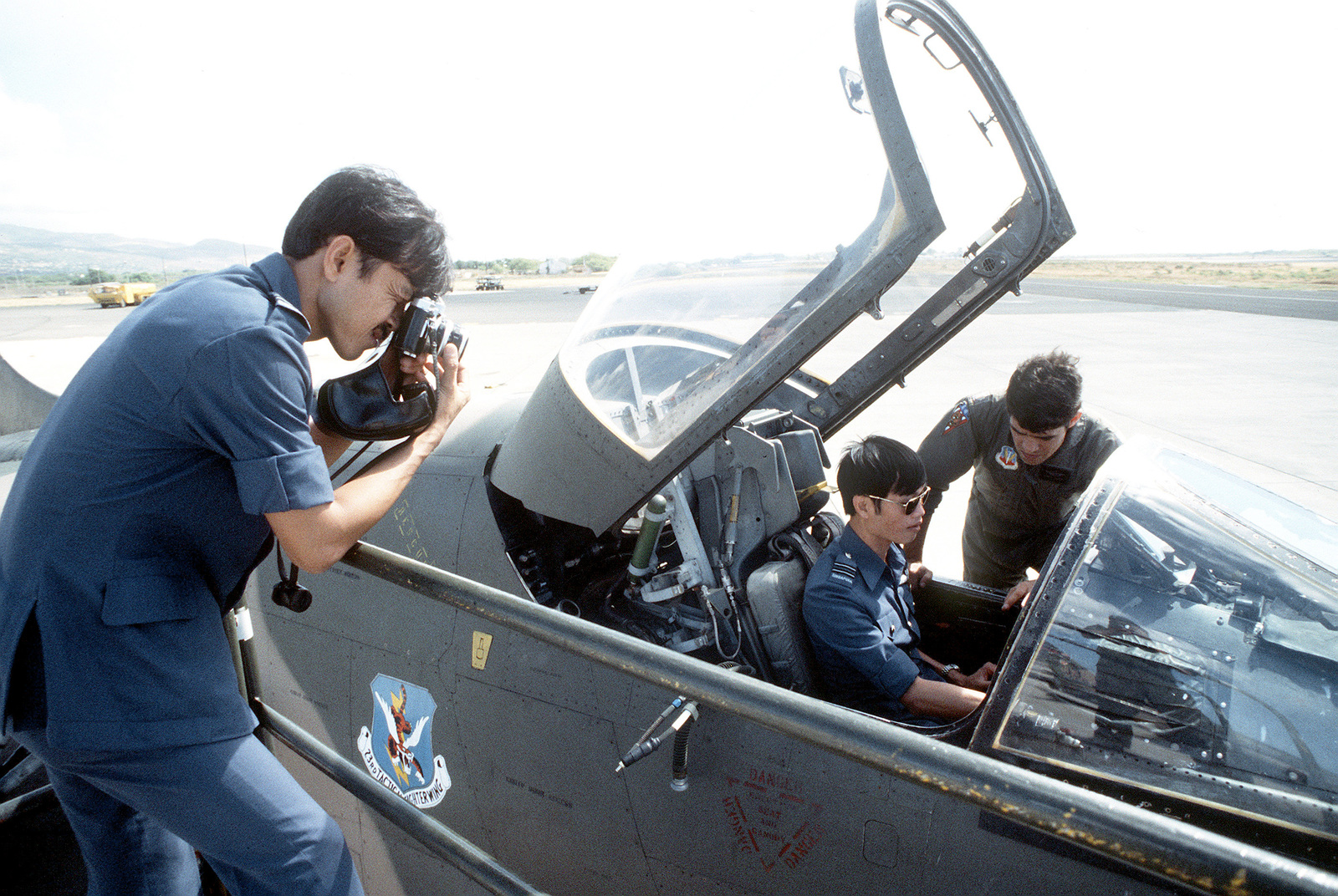 MAJ Lance Smith of the 23rd Tactical Fighter Wing Flying Tigers explains to Flight LT. Goh Chyelee of the Royal Singapore Air Force, cockpit features of an A-7D Corsair II aircraft during their participation in a joint exercise. Flight LT. Tom Wong of the Royal Singapore Air Force takes a photograph of the demonstration