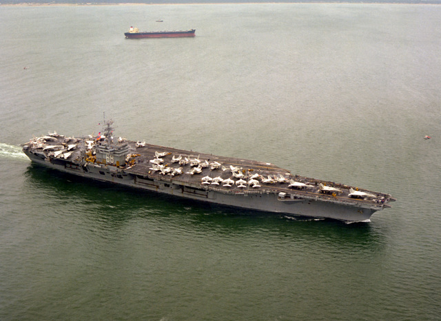 A starboard bow view of the nuclear-powered aircraft carrier USS NIMITZ (CVN-68) returning to home port in Norfolk, VA., following the May 26th aircraft crash on its flight deck. The crash, which occurred during the night landing of an EA-6B Prowler aircraft assigned to the carrier, killed 14 crewmen, injured 45 others and damaged several parked aircraft
