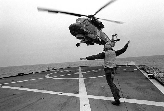 A flight deck crewman signals to an SH-2 Seasprite light airborne multi-purpose system (LAMPS) helicopter from Light Helicopter Anti-submarine Squadron 34 (HSL-34) during take-off