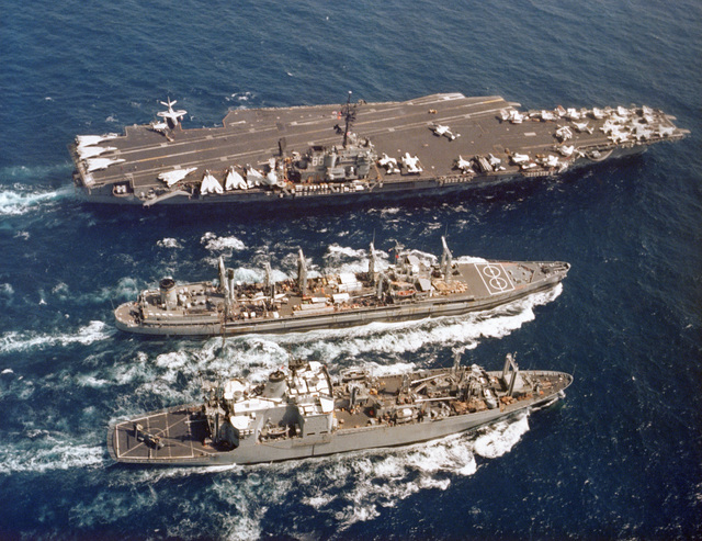 A high angle starboard view of the Kilauea class ammunition ship USS MOUNT BAKER (AE 34), the Mispillion class oiler USNS NAVASOTA (T-AO 106) and the aircraft carrier USS AMERICA (CV 66) during an underway replenishment operation