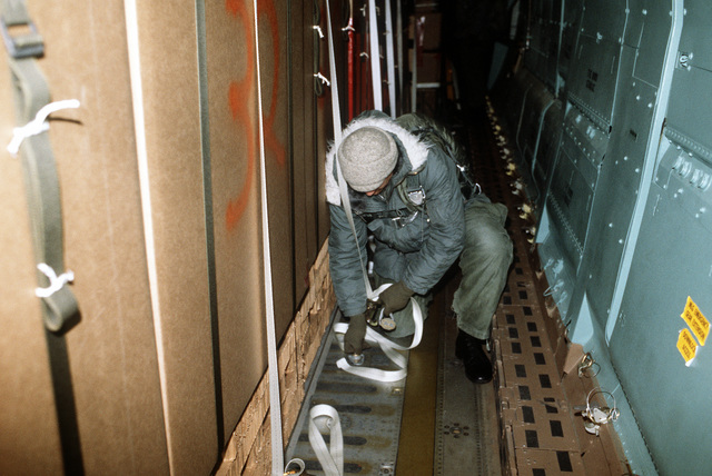A loadmaster removes restraining straps from the airdrop bundles. The airdrop will provide personnel stationed at McMurdo Station and South Pole, Antarctica, with fresh produce and supplies