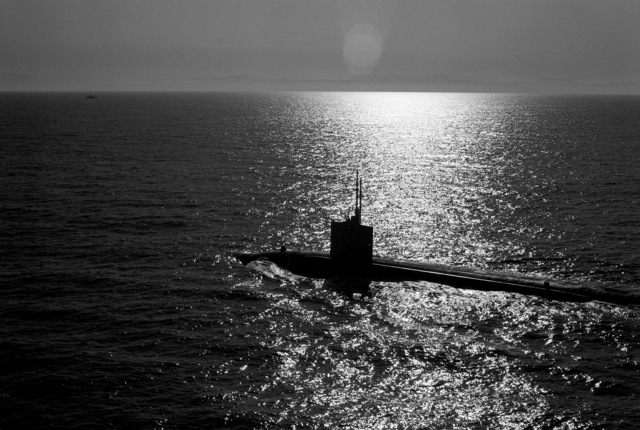 A silhouetted port quarter view of a nuclear-powered submarine underway