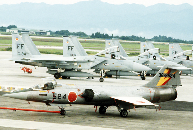 A view of a Japanese Air SelF Defense Force F-104 Starfighter aircraft and USAF F-4J Phantom aircraft on the flight line, during Exercise Cope North '81-3
