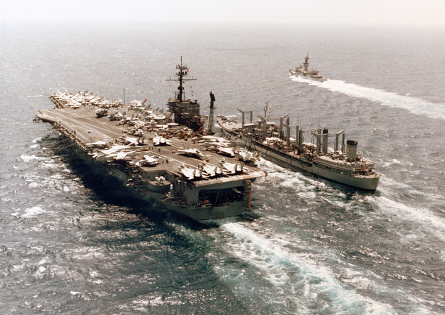 An aerial port quarter view of the aircraft carrier USS AMERICA (CV 66) and the Mispillion class oiler USNS NAVASOTA (T-AO 106) during an underway replenishment operation. A knox class frigate is visible in the background