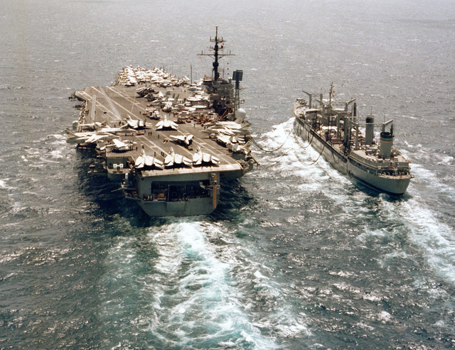 An aerial stern view of the aircraft carrier USS AMERICA (CV 66) and the Mispillion class oiler USNS NAVASOTA (T-AO 106) during an underway replenishment operation