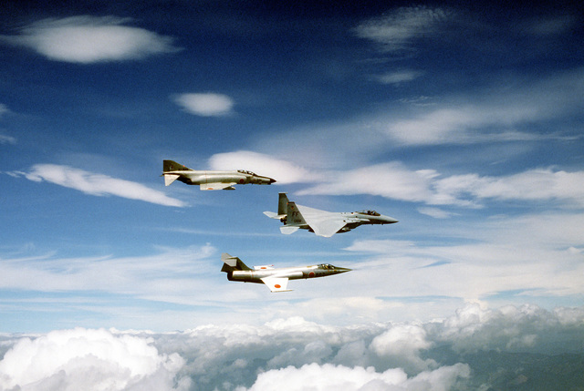 An air-to-air right side view of an F-15 Eagle (middle), a Japanese Air SelF Defense Force F-104J Starfighter (bottom), and an F-4J Phantom II aircraft (top), during Exercise Cope North '81-3