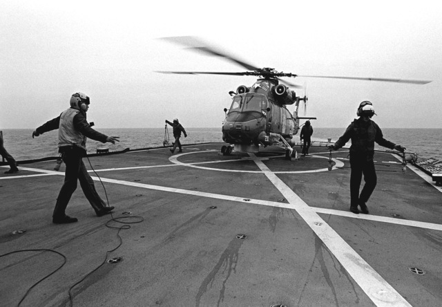 Flight deck crewmen aboard the destroyer USS JOHN HANCOCK (DD-981) prepare an SH-2 Seasprite light airborne multi-purpose system (LAMPS) helicopter from Light Helicopter Anti-submarine Squadron 34 (HSL-34) for lift-off