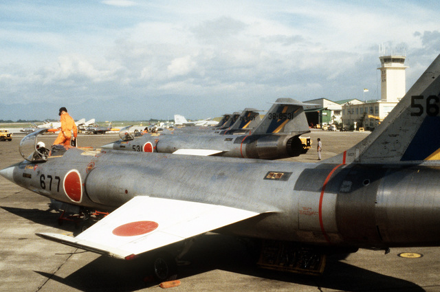 Left side view of Japanese Air SelF Defense Force F-104 Starfighter aircraft on the flight line, as JASDF crewmen do pre-flight maintenance during Exercise Cope North '81-3