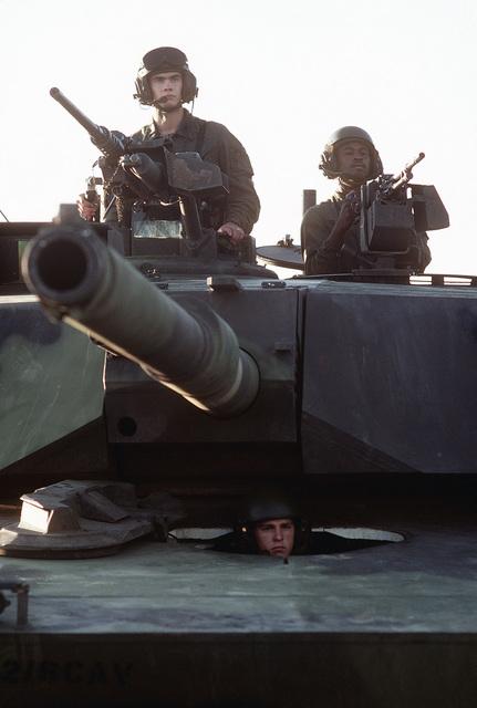 Members of an M1 Abrams main battle tank crew man the tank commander's M2.50-caliber machine gun, left, and the ammunition loader's M240 7.62 mm machine gun