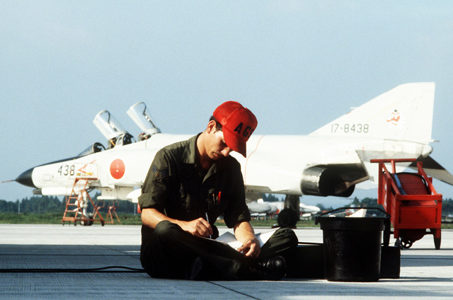 TSGT Jody Howard, a ground crewman, takes a break during Exercise Cope North '81-3. In the background is a Japan Air SelF Defense Force F-4J Phantom aircraft