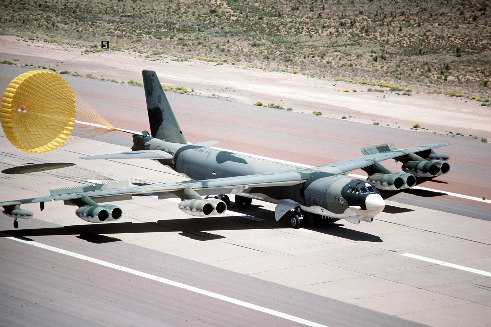A B-52H Stratofortress aircraft lands with its rear drag chute deployed during exercise Busy Prairie II