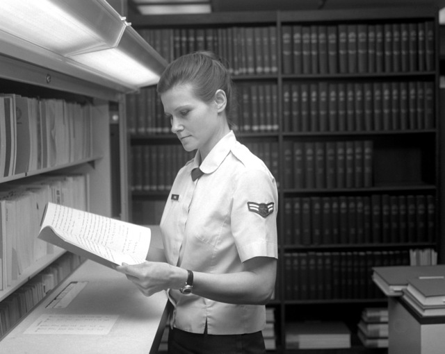 AIRMAN 1ST Class Grace Hyroc, a scientific aide, reads a report at the Air Force Human Resources Lab