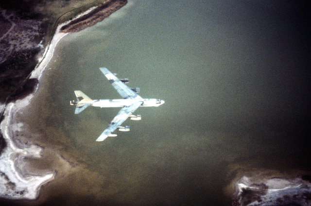 AN air-to-air right side view of a B-52H Stratofortress aircraft over a lake during exercise Busy Prairie II