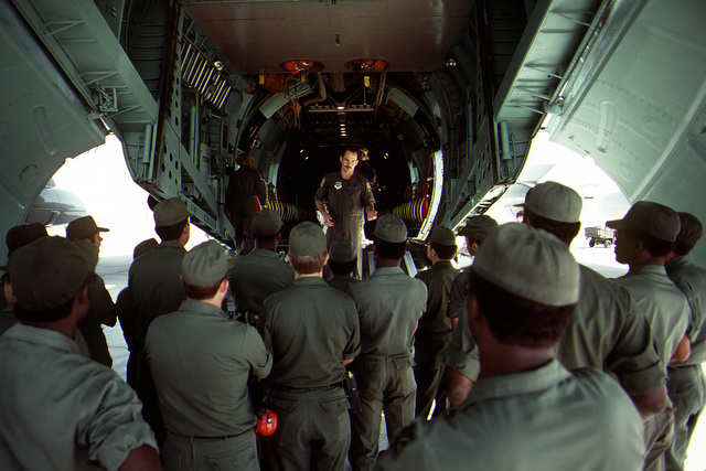 SSGT Ernesto X. Perez briefs Army troops on safe and proper methods for use of equipment to load cargo aboard a C-141 Starlifter aircraft during exercise Busy Prairie II. The airman is assigned to the military airlift squadron participating in the exercise