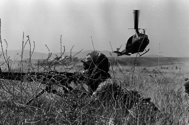 A Marine infantryman provides a field of covering fire with his M-60 machine gun during a field exercise. In the background, an Army UH-1 Iroquois helicopter prepares to land. The Marine is a member of Co. F, 2nd Bn., 1ST Marines