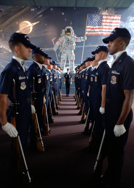 The U.S. Air Force Presidential Honor Guard Drill Team in formation near a depiction of astronaut Neil Armstrong's first moments on the moon. The depiction is inside the National Air and Space Museum of the Smithsonian Institute