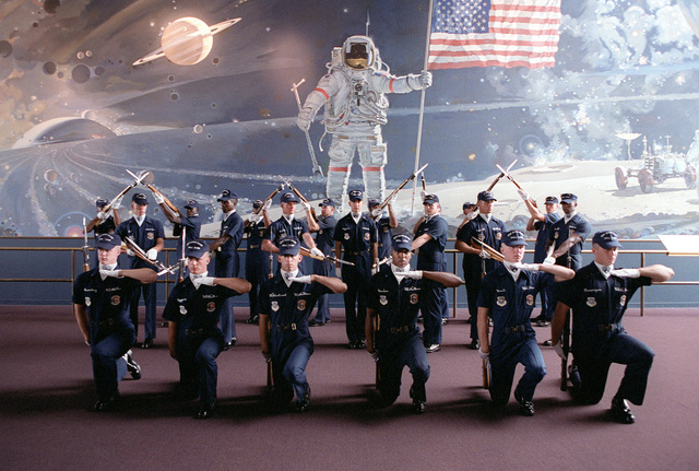 The U.S. Air Force Presidential Honor Guard Drill Team poses near a depiction of astronaut Neil Armstrong's first moments on the moon. The depiction is inside the National Air and Space Museum of the Smithsonian Institute