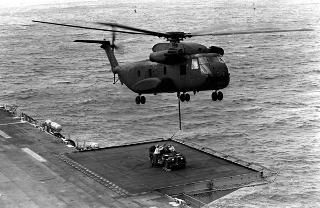 A Marine CH-46E Sea Knight helicopter from Marine Medium Helicopter Squadron 165 (HMM-165) hovers over a jeep in preparation for an external airlift from the amphibious assault ship USS BELLEAU WOOD (LHA-3) to a landing zone