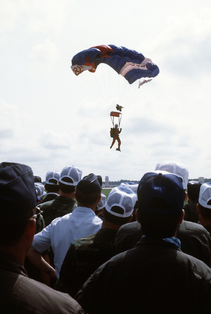 A paratrooper of the 82nd Airborne Division nears the ground, as airmen (foreground) watch, during the Volant Rodeo 1981 competition