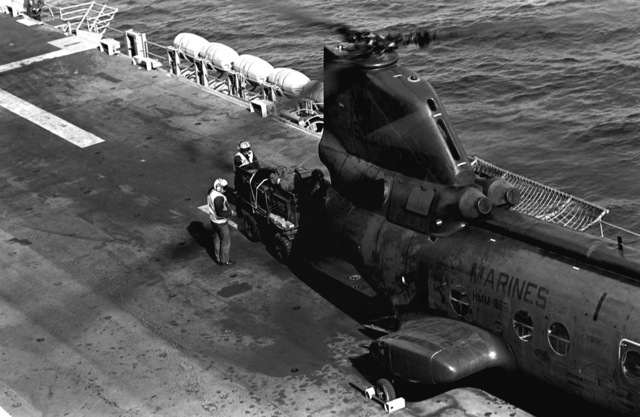Flight deck crewmen and Marines offload an M-274 lightweight vehicle from a Marine CH-46E Sea Knight helicopter aboard the amphibious assault ship USS BELLEAU WOOD (LHA-3). The Marines are a part of Battalion Landing Team, 2nd Battalion, 3rd Marines, who are returning from an operation held in Australia