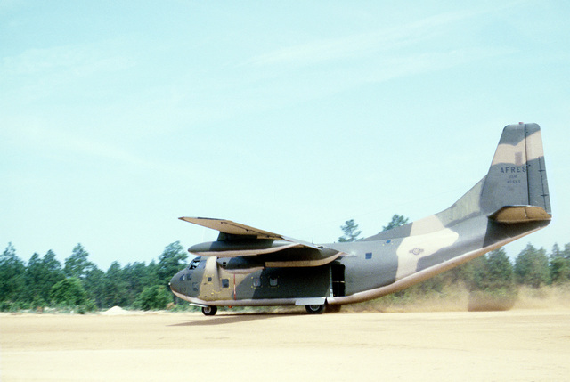 Left side view of a C-123 Provider aircraft during an assault landing on an unpaved strip. The aircraft is assigned to the Air Force Reserve, involved in the Volant Rodeo 1981 competition