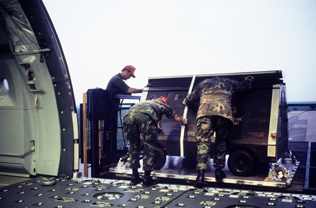 Interior view of a KC-10 Extender aircraft as cargo is positioned on a Cochran Loader