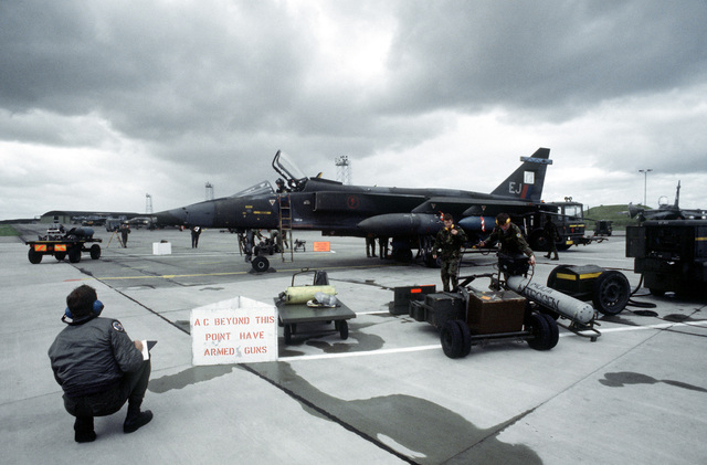 A judge observes maintenance performance of a Royal Air Force team on a Jaguar aircraft during the quick turn phase of the Strike Command Bombing Competition between the U.S. and RAF