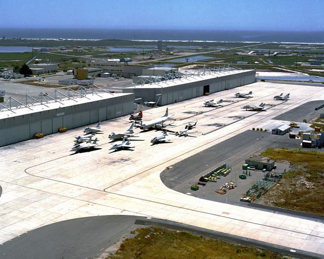 A view of the runway and hangars at Pacific Missile Test Center. Several aircraft are parked on the runway including an F/A-18 Hornet, F-14 Tomcat, P-3 Orion, F-4J Phantom II and a CH-46 Sea Knight helicopter